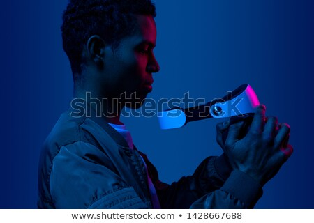 man standing in virtual reality helmet before dark background stock photo © chesterf