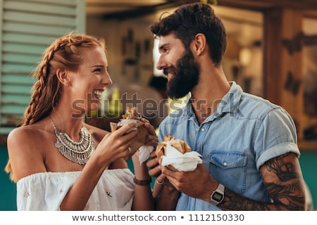 Young man and woman eating burgers in the street Stock photo © deandrobot
