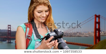 woman with backpack and camera over golden gate Stock photo © dolgachov