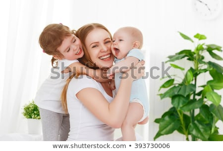 mother and two children in the bedroom on the bed stock photo © lopolo