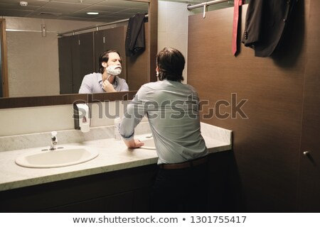 Business Man Shaving In Office Bathroom After Early Morning Commute Stock photo © diego_cervo