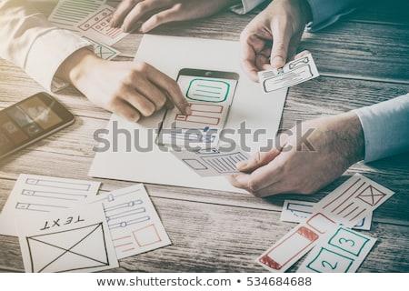 designer with smartphone working on user interface Stock photo © dolgachov