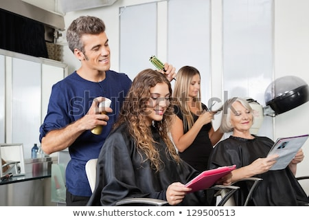 Stockfoto: Female Hairdresser Setting Up Clients Hair In Beauty Salon