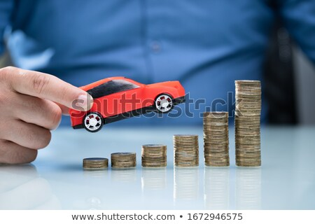 Person Holding Car Over Rising Stacked Coins Stock photo © AndreyPopov