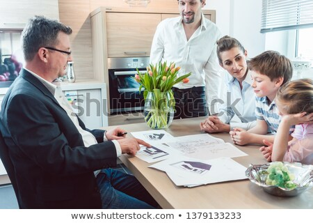 Family planning their kitchen with experienced expert in the shop Stock photo © Kzenon