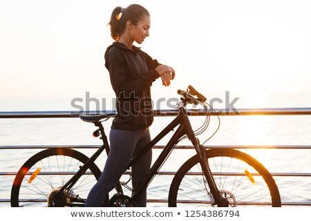 photo of pretty sportswoman standing with bicycle on boardwalk stock photo © deandrobot