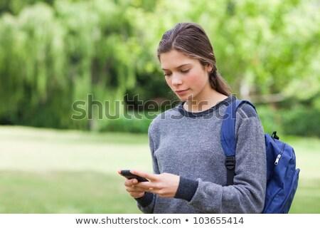 Fiatal higgadt lány mobiltelefon küld szöveg Stock fotó © galitskaya