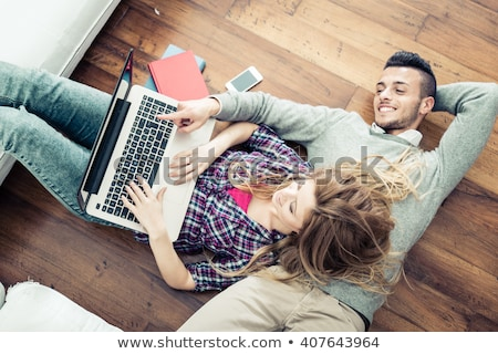 Smiling couple man and woman in casual clothing sitting on sofa  Stock photo © deandrobot