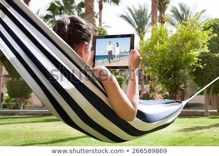 Nő függőágy néz videó tabletta tengerpart Stock fotó © AndreyPopov