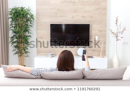 Young beautiful woman watching TV on a sofa at home Stock photo © Lopolo