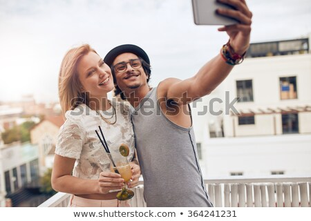 friends with drinks taking selfie at rooftop party Stock photo © dolgachov