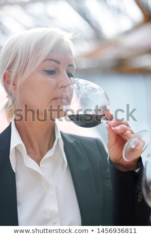 Pretty sommelier checking flavor, smell and quality of red wine Stock photo © pressmaster