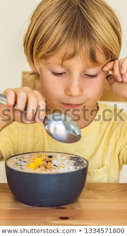 Foto stock: Happy Boy Sitting And Eating A Fresh Smoothie Bowl With Mango Dragon Fruit Granola And Chia Seeds