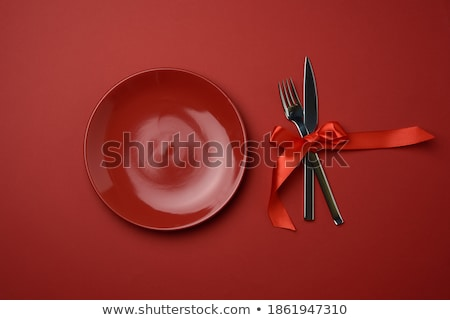 cutlery tied with red ribbon on set of plates Stock photo © dolgachov