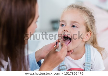 Little girl opening mouth in front of clinician examining her throat Stock photo © pressmaster
