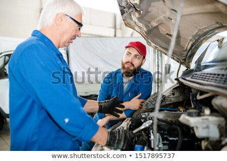 young bearded worker of technical service looking at his mature colleague stock photo © pressmaster