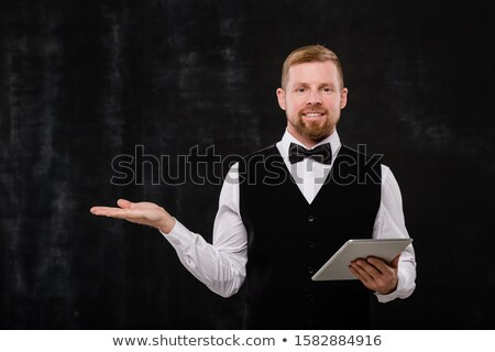 Happy young bearded waiter with digital tablet showing you where to go Stock photo © pressmaster