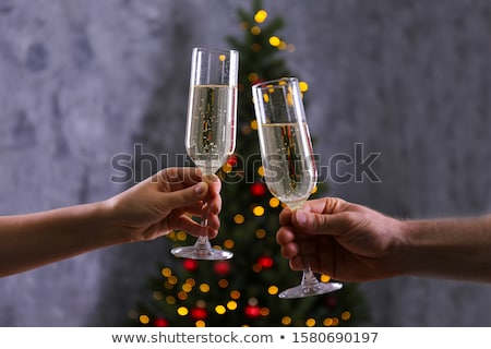 Hands of young couple clinking with flutes of champagne on xmas background Stock photo © pressmaster