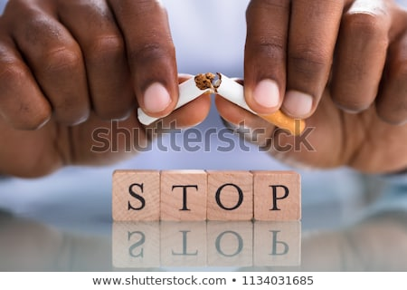 Person's Hand Breaking Cigarette Over The Stop Blocks Stock photo © AndreyPopov