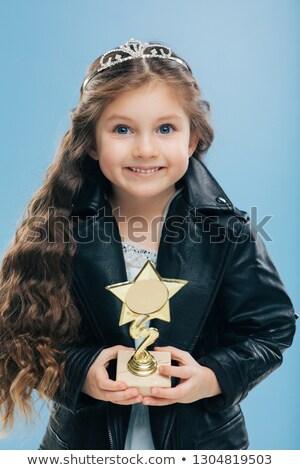 Positive smiling European child with blue eyes, long crisp hair, holds reward in form of star, wears Stock photo © vkstudio