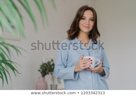 Waist up shot of pleasant looking young woman dressed in striped pyjamas, drinks hot beverage after  Stock photo © vkstudio