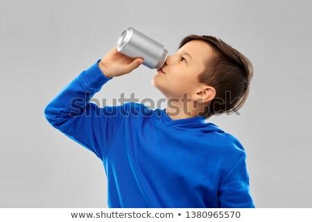 Ragazzo blu bere soda tin può Foto d'archivio © dolgachov