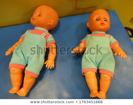 Stock photo: lying down baby girl with a doll