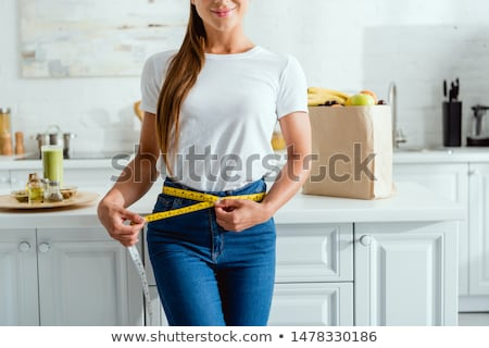 Woman measuring waist with a tape measure Stock photo © Nobilior