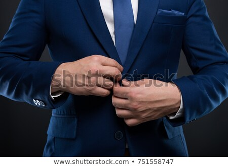 Stock photo: young business man buttons his jacket