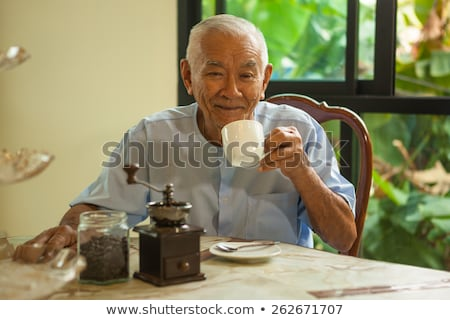 asian senior man with vintage coffee grinder stock photo © witthaya