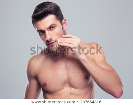 Man cleaning face skin with batting cotton pads Stock photo © deandrobot