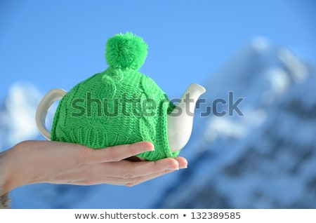 tea pot in the knotted cap in the hands stock photo © dashapetrenko