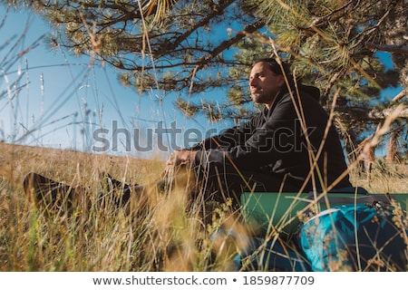 Сток-фото: Young Caucasian Man With Backpack Sitting On The Top Of Hill