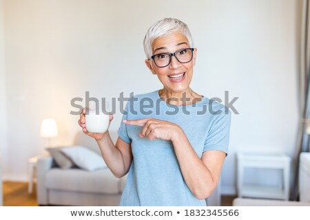 Woman drinking a glass of milk while looking the camera Stock photo © wavebreak_media