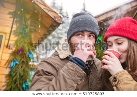 Pretty young woman drinking hot beverage on christmas market  Stock photo © deandrobot