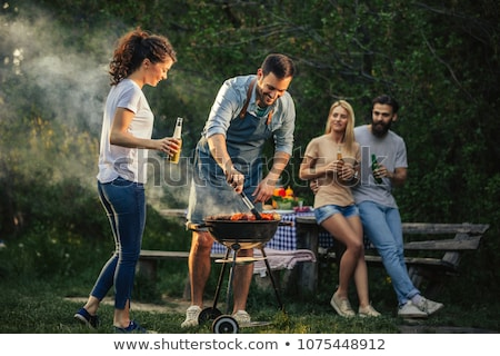 Stock photo: Barbecue in nature, group of people preparing sausages on fire