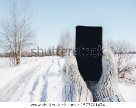 Woman in wool gloves hold smart-phone Stock photo © adamr