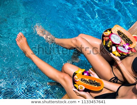 Friendly young woman relaxing near a pool Stock photo © dash