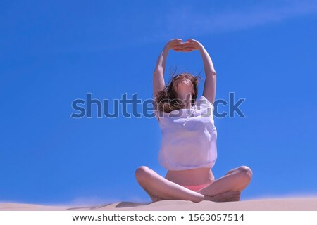 girl in sunglasses and blue swimsuit posing with hands up stock photo © deandrobot