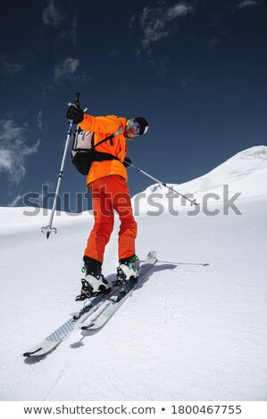 Young man in snowy mountain landscape looks into the camera Stock photo © kb-photodesign