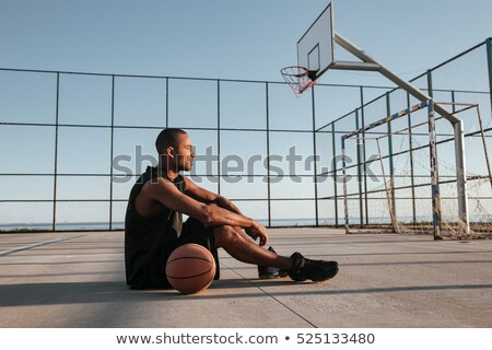 Tired afro american sports man resting on a basketball Stock photo © deandrobot