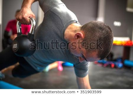 Fiatalember emel súlyzók crossfit tornaterem férfi Stock fotó © Yatsenko