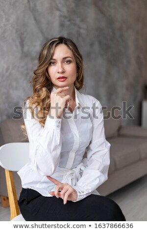 Beautiful blonde lady sitting indoors dressed in white dress Stock photo © deandrobot