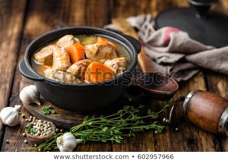 Meat stewed with carrots in sauce and spices in cast iron pot on dark wooden rustic background Stock photo © yelenayemchuk