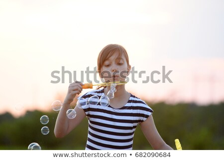 Girl on bale of hay blowing bubbles Stock photo © IS2