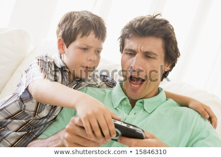 Man in living room playing handheld videogame smiling stock photo © monkey_business