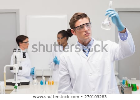 Scientist in white coat holding beaker Stock photo © bluering