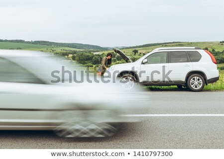 Woman standing on hood of SUV Stock photo © IS2