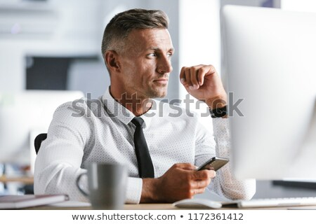 image of serious businessman 30s wearing white shirt and tie sit stock photo © deandrobot