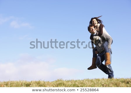 Man Giving His Wife A Piggy Back Ride In Park Stock photo © monkey_business